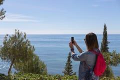 Mulher que toma a foto da natureza e do mar Foto de Stock