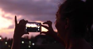 Mulher que toma a foto do céu do por do sol filme