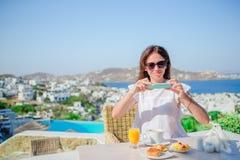Mulher que toma a foto do café da manhã usando seu telefone com vista surpreendente de Mykonos Menina que toma imagens do aliment imagens de stock royalty free