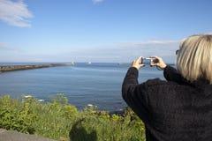 Mulher que toma a foto em Whitley Bay foto de stock