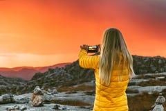 A mulher que toma a foto pelo smartphone de montanhas do por do sol ajardina Foto de Stock Royalty Free