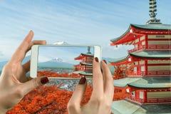 Mulher que toma a fotografia com uma câmera esperta do telefone no Mt Monte Fuji com cores da queda em japão imagens de stock royalty free