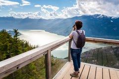Mulher que toma fotos com sua câmera de DSRL da parte superior de uma montanha foto de stock