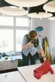Mulher que toma fotos da roupa do cão na oficina da roupa foto de stock