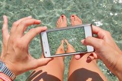 Mulher que toma fotos de seus pés no mar. Fotos de Stock