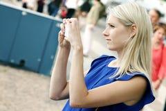 Mulher que toma a imagem com telefone celular na rua Imagens de Stock