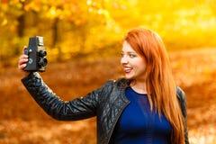 Mulher que toma a imagem da foto com a câmera velha exterior Imagens de Stock Royalty Free