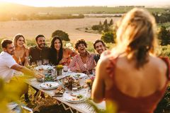 Mulher que toma a imagem dos amigos que têm o partido de jantar foto de stock royalty free