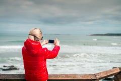 Mulher que toma imagens com telefone celular Imagens de Stock