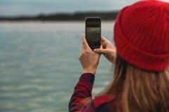 Mulher que toma imagens com um telefone celular Fotografia de Stock Royalty Free