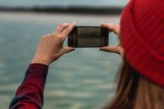 Mulher que toma imagens com um telefone celular imagens de stock