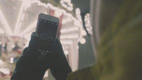 Mulher que toma imagens da cena europeia do carrossel em Smartphone 4K Menina que aprecia a época natalícia do inverno vídeos de arquivo