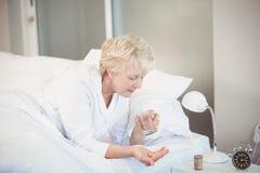 Mulher que toma a medicina ao descansar na cama imagem de stock royalty free