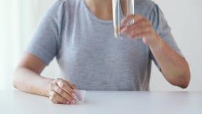 Mulher que toma a medicina e a água potável video estoque