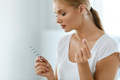 Mulher que toma a medicina Menina bonita com bloco do comprimido com comprimidos Imagens de Stock Royalty Free