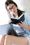 Mulher que toma notas em casa Fotos de Stock