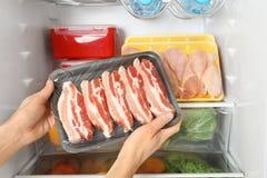 Mulher que toma o bacon cru do refrigerador imagens de stock