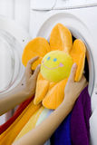 Mulher que toma o brinquedo macio da máquina de lavar Foto de Stock Royalty Free
