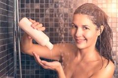 Mulher que toma o champô de derramamento do cabelo do chuveiro em sua mão imagens de stock royalty free