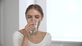 Mulher que toma o comprimido, água potável do vidro no interior branco video estoque