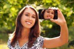 Mulher que toma o retrato do auto com câmera do telefone