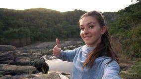 Mulher que toma o selfie e que mostra o polegar acima da cachoeira próxima em Dalat, Vietname vídeos de arquivo