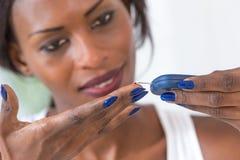 Mulher que toma o teste do diabetes com glucometer Fotos de Stock Royalty Free