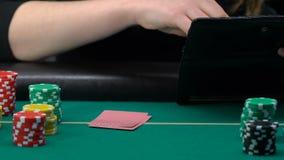 Mulher que toma a pilha dos dólares da bolsa e da aposta tudo olhando seus cartões video estoque