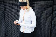 Mulher que toma um exercício do formulário da ruptura usando o telefone celular Imagem de Stock
