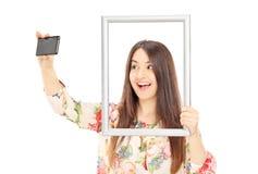 Mulher que toma um selfie atrás de uma moldura para retrato Fotografia de Stock