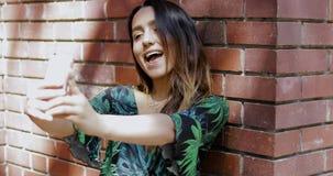 Mulher que toma um selfie na frente de uma parede de tijolo vídeos de arquivo