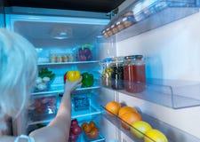 Mulher que toma uma pimenta doce fresca de um refrigerador fotografia de stock