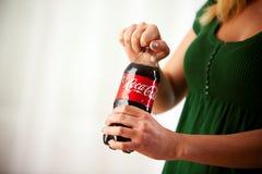 Mulher que torce o tampão fora da garrafa da coca-cola Imagem de Stock Royalty Free