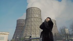 Mulher que tosse perto das chaminés da fábrica vídeos de arquivo