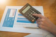 Mulher que trabalha com a calculadora para calcular números Despesas c imagem de stock