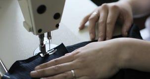 Mulher que trabalha com máquina de costura, fim acima vídeos de arquivo