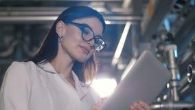 Mulher que trabalha com o PC da tabuleta na fábrica video estoque