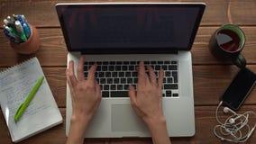 Mulher que trabalha com o portátil colocado na mesa de madeira video estoque