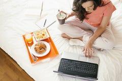Mulher que trabalha com seu laptop e que come o café da manhã Fotografia de Stock Royalty Free