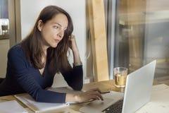 Mulher que trabalha com seu portátil que pensa comendo o café dentro de um co imagens de stock royalty free