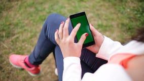 Mulher que trabalha com a tela do verde do parque do smartphone video estoque