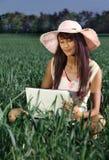 Mulher que trabalha com um portátil exterior Fotos de Stock Royalty Free