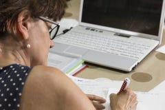Mulher que trabalha em manuscritos, em dobradores e em originais do computador foto de stock