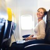 Mulher que trabalha em seu computador portátil a bordo de um avião Imagem de Stock