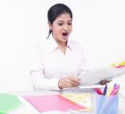 Mulher que trabalha em sua mesa de escritório Fotos de Stock Royalty Free