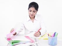 Mulher que trabalha em sua mesa de escritório Foto de Stock Royalty Free