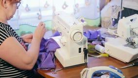 Mulher que trabalha em uma máquina de costura A mulher prepara a tela costurando video estoque
