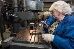 Mulher que trabalha em uma máquina de perfuração Fotos de Stock Royalty Free