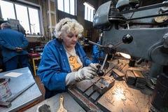 Mulher que trabalha em uma máquina de perfuração Imagens de Stock