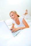Mulher que trabalha na cama imagem de stock royalty free
